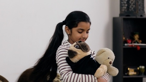 Medium shot of a cute little girl adorably swaying her teddy bears in her arms