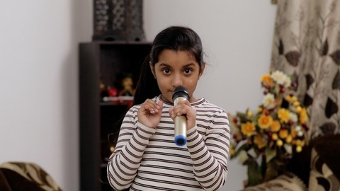 Cute little kid enjoying and having fun in singing karaoke - kids lifestyle concept