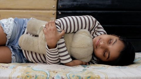 Medium shot of a cute little girl sleeping in her bed while hugging her teddy bear
