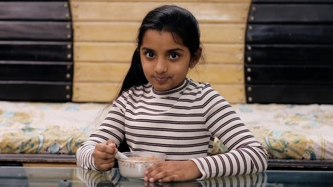 A medium shot of a cute little Indian girl smiling and eating her cereal at home