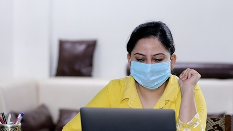 Sick Indian woman in a surgical mask busy over a video call - lifestyle concept