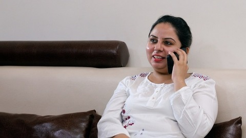 A middle-aged woman happily talking to her friend on a phone call - leisure time