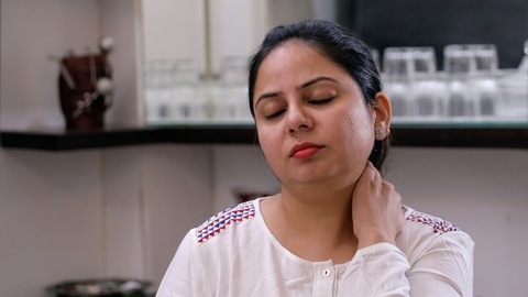 Pretty Indian woman suffering from severe neck pain - health and medical concept