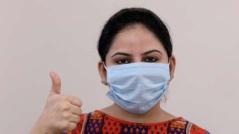 Pretty Indian female wearing a surgical mask to protect herself from coronavirus