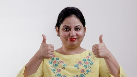 Pretty Indian female happily gesturing thumbs-ups against the white background