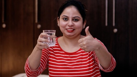 Portrait of a beautiful Indian female holding a glassful of freshwater - casual wear