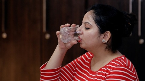 Medium shot of a pretty middle-aged woman drinking a glass full of freshwater