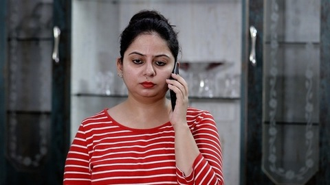 Portrait of an upset Indian female receiving a piece of bad news on smartphone