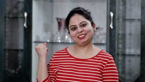 Excited Indian woman happily doing winning gesture against a blurred background