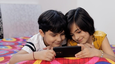 Cute little brother and sister happily watching cartoons together on a smartphone