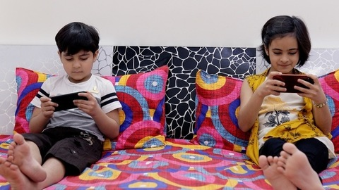 Siblings happily playing games on mobiles where the sister is unhappy to lose