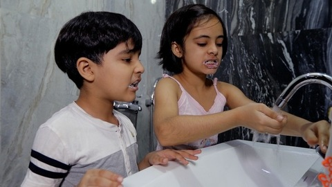 Young siblings brushing their teeth properly in a bathroom - hygiene concept