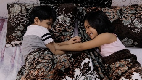 Cute little siblings happily playing with each other at night before going to bed