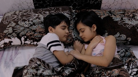 Cute little siblings peacefully sleeping together while holding the hands of each other