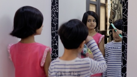 Adorable little siblings combing their hair while standing in front of a mirror