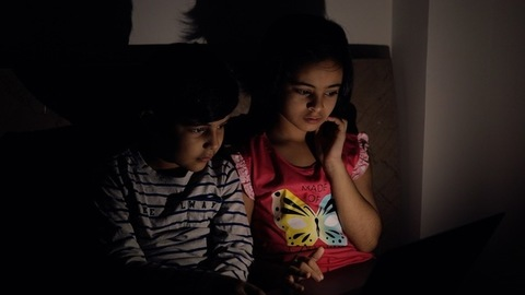 Indian siblings watching a movie on the laptop in the darkroom - Screen time. Screen Addiction