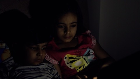 Young brother and sister happily watching movies in the darkness - lifestyle kids