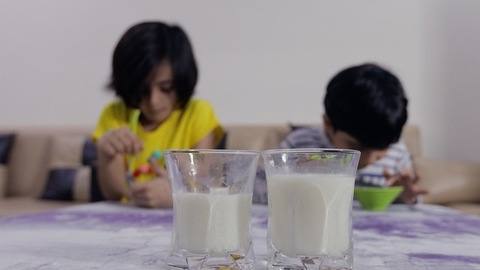 Adorable little siblings playfully teasing each other while having their breakfast