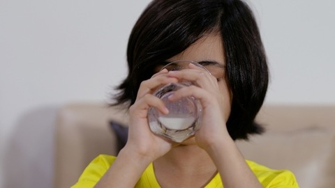 Closeup shot of an attractive little girl drinking a glassful of milk at home