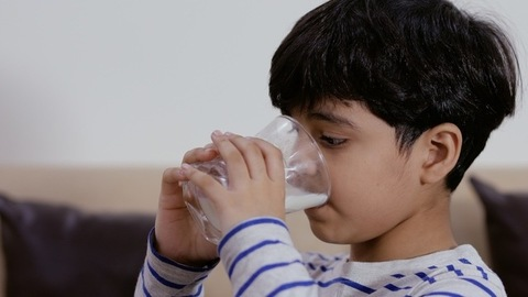 Close-up shot of a small adorable boy drinking a glass of milk at his home