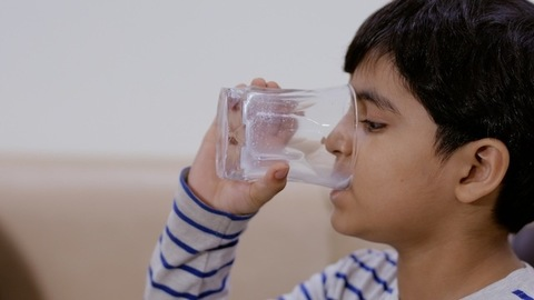 Closeup shot of a handsome Indian boy drinking a glassful of milk at home