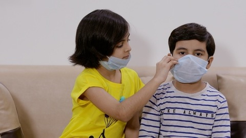 Sister helping her brother wear a mask properly before wearing it herself