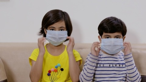 Two adorable children opening and discarding their masks happily