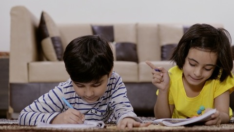 Little sister studying and helping her small brother to complete his homework