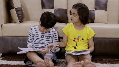 Adorable small siblings studying together while sister completing her work