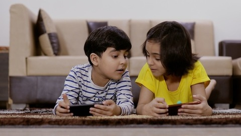 Young siblings lying on carpet and playing games on their smartphones