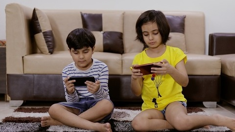 Siblings playing games on their smartphones and sister showing her screen
