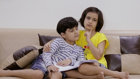 Small sister narrating a story to her younger brother while leaning on each other