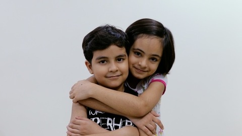 A beautiful little sister coming and hugging her younger brother with a smile