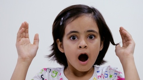 A small girl removing her hands from eyes showing surprise gesture