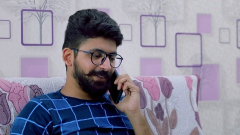 Closeup of a handsome Indian man happily talking to a friend over a phone call