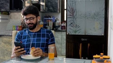 Bearded Indian guy in white earphones enjoying music while having breakfast