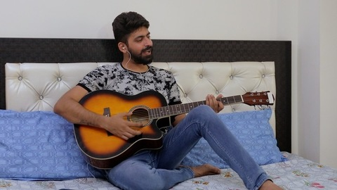 A bearded Indian man practicing his new lyrical song on guitar - music concept