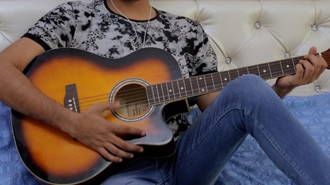 Portrait shot of a handsome young musician enjoying singing while playing guitar