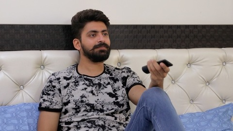Portrait shot of a bearded Indian guy in trendy casual wear watching television