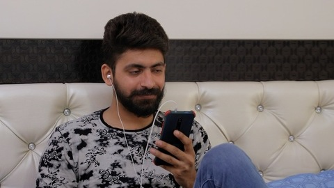 Handsome Indian guy happily doing distance video call to his family and friends