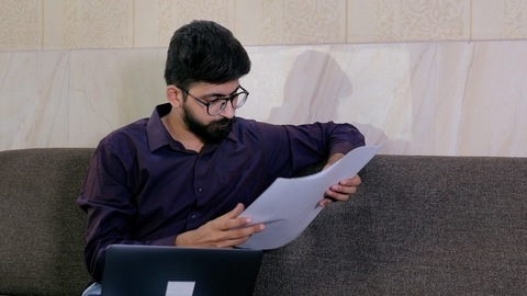 Young businessman working with paper documents and laptop at the home office