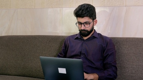 Handsome Indian guy working on his laptop during the Covid-19 pandemic time