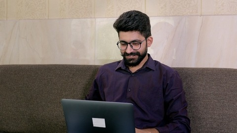 The excited young guy doing winning gesture while using his laptop - formal wear
