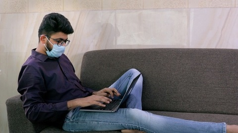 Side view shot of a sick Indian man in medical face mask working on his laptop