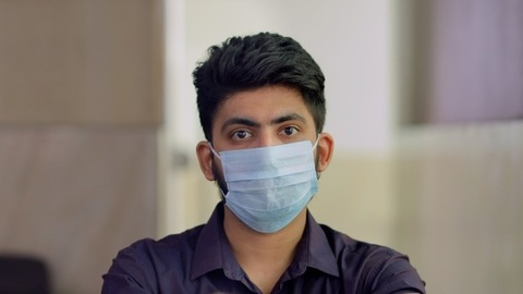 Handsome Indian guy wears a surgical mask to protect himself from coronavirus