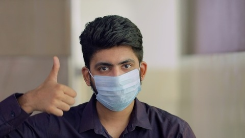 Closeup shot of a young man using a medical mask during the Covid-19 pandemic
