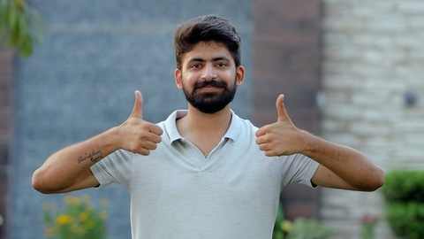Handsome Indian guy happily gesturing thumbs-ups against a blurred wall background