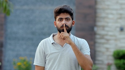 Portrait of a young attractive guy gesturing shh, secrecy or silence - casual wear