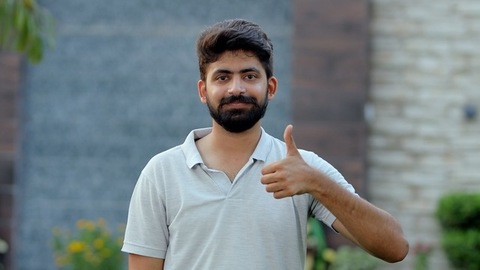 Attractive young man showing a thumbs-up sign while smiling towards the camera