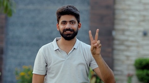 Handsome Indian guy showing a peace sign with a wide toothy smile on his face